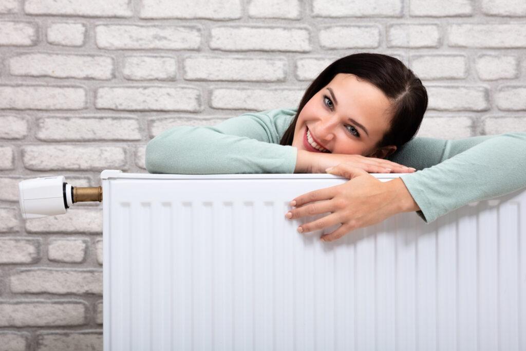 woman leaning on heating radiator
